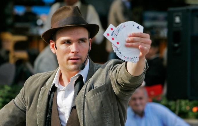 Charlie Caper håller upp en magisk kortlek