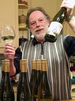 Krögaren Arne Nilsson håller upp en vinflaska
