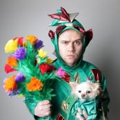 En man i en maskeraddräkt av en drake håller fram blommor